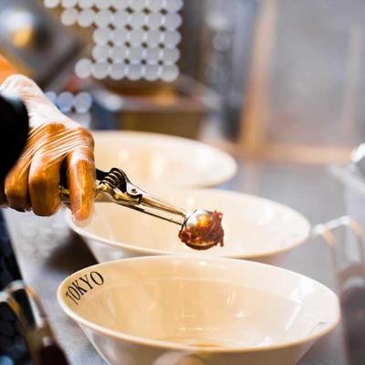 Kitchen image of RAKKAN RAMEN, miso is poured into the ramen bowl.