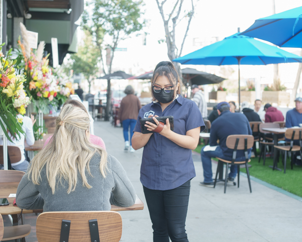 Long Beach Opening: a waitress is taking orders.