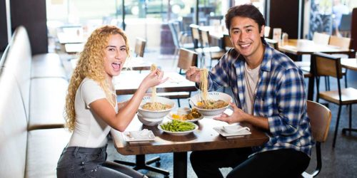 Pictures at RAKKAN Ramen Redondo Beach, 2 customers are eating ramen and smiling.